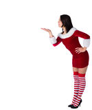 Pretty brunette in santa outfit blowing over hand Stock Images