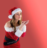 Pretty brunette in santa outfit blowing over hands Royalty Free Stock Photo
