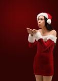 Pretty brunette in santa outfit blowing over hands Stock Photography