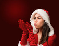 Pretty brunette in santa outfit blowing over hands Royalty Free Stock Images