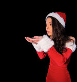 Pretty brunette in santa outfit blowing over her hands Royalty Free Stock Photography