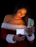 Pretty brunette in santa outfit opening gift Stock Photos
