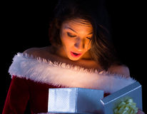 Pretty brunette in santa outfit opening gift Royalty Free Stock Photography
