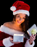 Pretty brunette in santa outfit opening gift Royalty Free Stock Photos