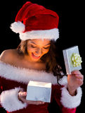 Pretty brunette in santa outfit opening gift Stock Images