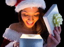 Pretty brunette in santa outfit opening gift Royalty Free Stock Image