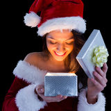 Pretty brunette in santa outfit opening gift Stock Photo