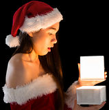 Pretty brunette in santa outfit opening a gift Stock Photo