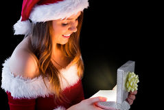 Pretty brunette in santa outfit opening gift Stock Image