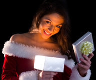 Pretty brunette in santa outfit opening gift and smiling at camera Stock Image