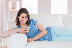 Pretty brunette sending a text on the couch Royalty Free Stock Photo