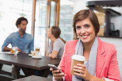 Pretty brunette sending a text drinking coffee Royalty Free Stock Photography