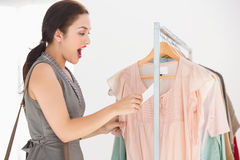 Pretty brunette shocked at price of shirt Royalty Free Stock Photography