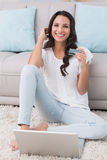 Pretty brunette shopping online with laptop Royalty Free Stock Images