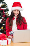 Pretty brunette shopping online with laptop Stock Image
