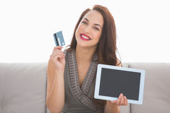 Pretty brunette showing credit card and screen of laptop Royalty Free Stock Photography