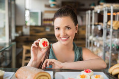 Pretty brunette showing a cupcake Royalty Free Stock Photo