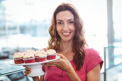 Pretty brunette showing plate of pastries Royalty Free Stock Photos