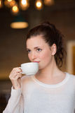 Pretty brunette sipping cup of coffee Stock Photos