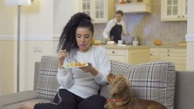 Cute girl eats salad while boyfriend cooks the dinner. Pretty brunette sits on sofa in the room with her dog and eats a fresh salad. The dog looks pleadingly on stock video footage