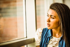 Pretty brunette sitting alone unsmiling Stock Image
