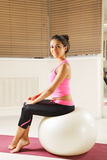 Pretty brunette sitting on a ball Royalty Free Stock Photography