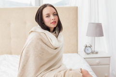 Pretty brunette sitting on bed Stock Photos