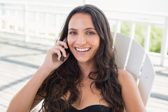 Pretty brunette sitting on a chair and calling with her mobile phone Royalty Free Stock Images
