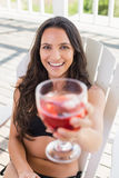 Pretty brunette sitting on a chair and drinking cocktail Royalty Free Stock Photo