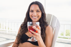 Pretty brunette sitting on a chair and drinking cocktail Stock Images