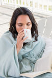Pretty brunette sitting on a chair and drinking coffee Stock Photography
