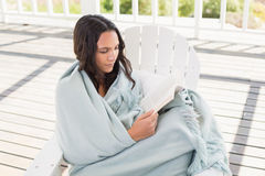 Pretty brunette sitting on a chair and reading a book. In patio Royalty Free Stock Image