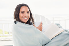 Pretty brunette sitting on a chair and reading a book Stock Photos