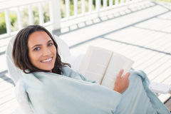 Pretty brunette sitting on a chair and reading a book Stock Image