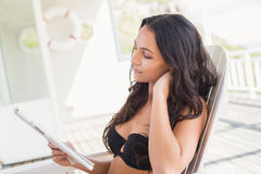 Pretty brunette sitting on a chair and reading magazine. In patio Royalty Free Stock Images