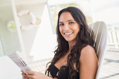 Pretty brunette sitting on a chair and reading magazine Royalty Free Stock Photos