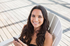 Pretty brunette sitting on a chair and texting with her mobile phone Royalty Free Stock Photography
