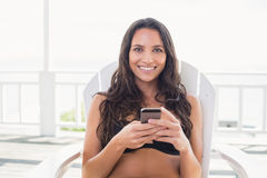 Pretty brunette sitting on a chair and texting with her mobile phone Stock Photography