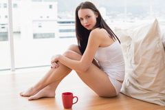 Pretty brunette sitting on floor with mug Royalty Free Stock Photography