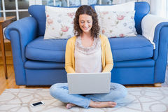 Pretty brunette sitting on the floor and using her laptop Stock Photo