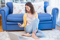 Pretty brunette sitting on the floor and using her smartphone Royalty Free Stock Photo