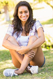 Pretty brunette sitting in the grass Royalty Free Stock Image