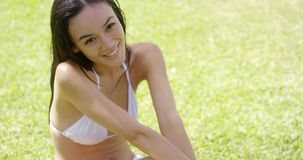 Pretty brunette sitting on green lawn stock video