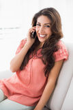 Pretty brunette sitting on her couch on a phone call Stock Photography