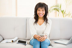 Pretty brunette sitting on her couch using her smartphone. At home Royalty Free Stock Photography