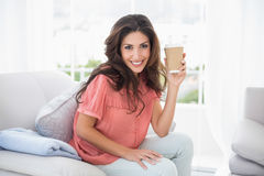 Pretty brunette sitting on her sofa holding disposable cup Royalty Free Stock Photos