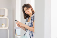 Pretty brunette sitting beside her window sending a text Royalty Free Stock Photography