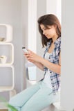 Pretty brunette sitting beside her window sending a text Stock Photography