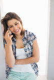 Pretty brunette sitting beside her window talking on phone Royalty Free Stock Photography