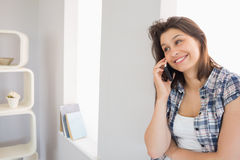 Pretty brunette sitting beside her window talking on phone Royalty Free Stock Image